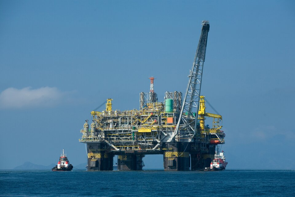 Na zdjęciu platforma wiertnicza. Zespół urządzeń technicznych opartych na czterech kolumnach stojących wwodzie. Po obu stronach platformy statki, niewielkich rozmiarów wporównaniu zplatformą.