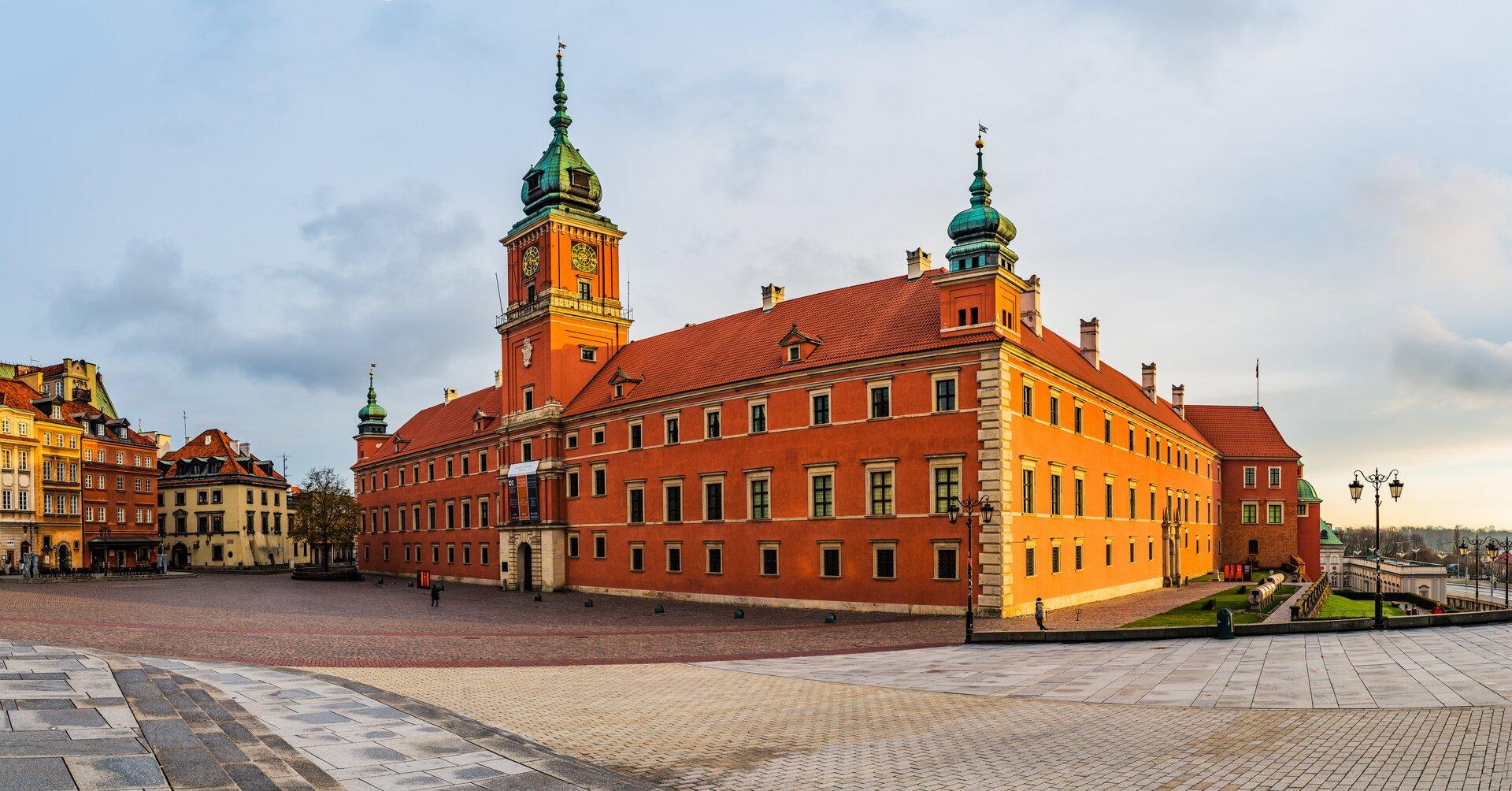 Ilustracja przedstawia zamek królewski wWarszawie. Budynek ten znajduje wcentrum fotografii. Ma pomarańczową elewację, oraz wysoką wieżę zegarową. Obok budynku są widoczne kamienice oraz chodnik.