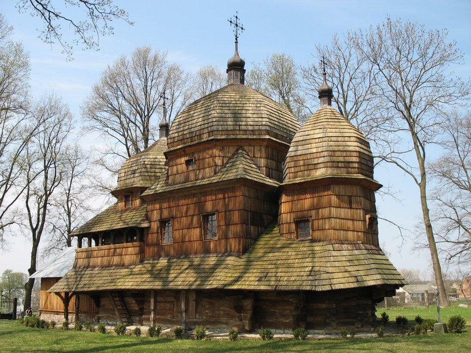 Drewniana cerkiew otoczona drzewami. świątynia ma trzy części skopułami na dachu. na każdej zkopuł jest widoczny krzyż.