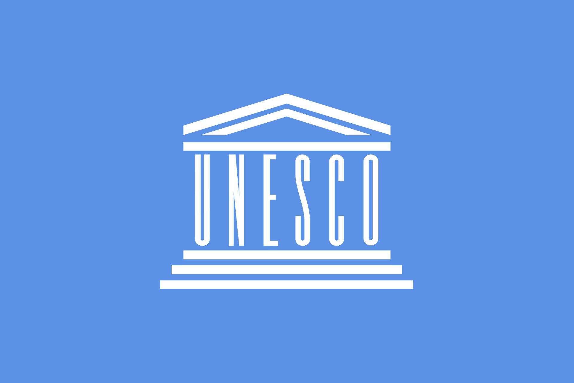 Ilustracja przedstawia białe logo organizacji UNESCO na błękitnym tle. Logo wkształcie budynku. Górna część to spadzisty trójkątny dach wsparty na białej poziomej linii. Poniżej pionowo ustawione litery UNESCO. Litery tworzą kolumny budynku. Poniżej liter trzy poziome białe linie. Każda linia poniżej jest nieco dłuższa od poprzedniej. Linie to schody prowadzące do budynku.