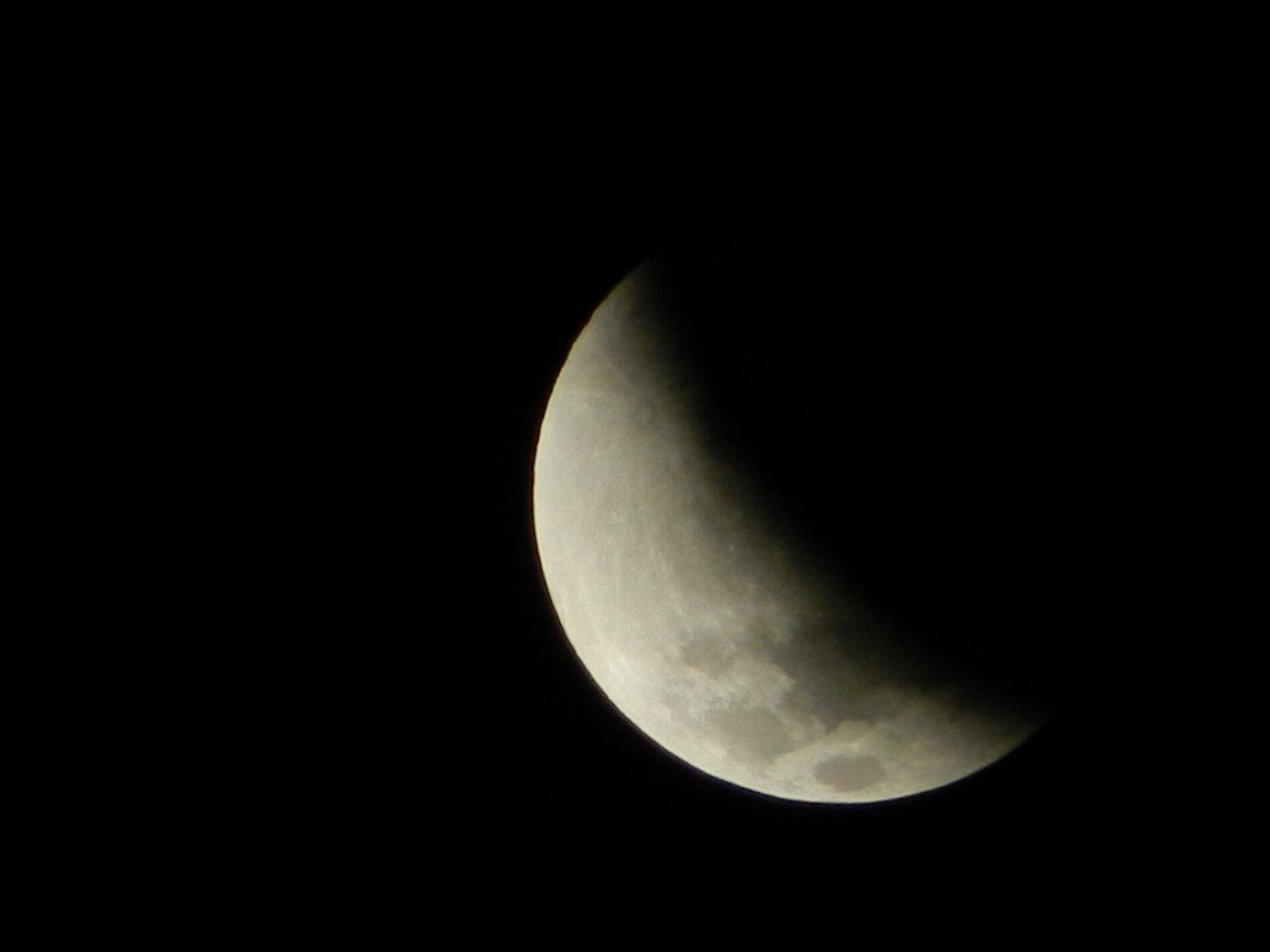 Fotografia prezentuje okrągły biało-szary księżyc na tle czarnego nieba. Tarcza księżyca, wprzeszło połowie swojej wielkości, jest zasłonięta cieniem Ziemi.