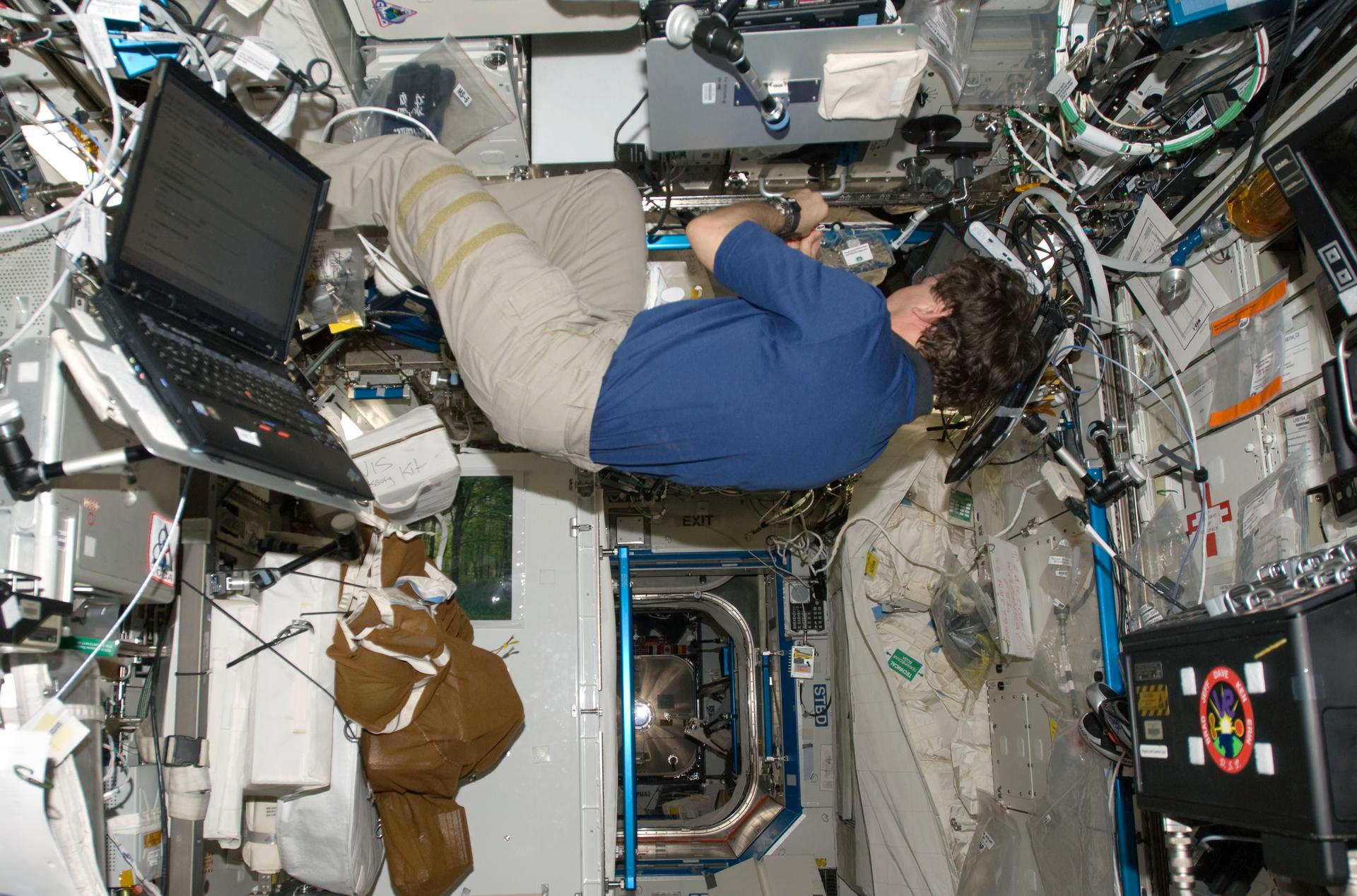Fotografia wykonana zgóry, ukazuje astronautę wstanie nieważkości wniewielkim pomieszczeniu na stacji kosmicznej. Astronauta widoczny ze swojego lewego boku manipuluje przy sprzęcie. Na ścianach pomieszczania przytwierdzone różne sprzęty oraz kable. Poniżej astronauty widoczne przejście do następnego pomieszczenia.
