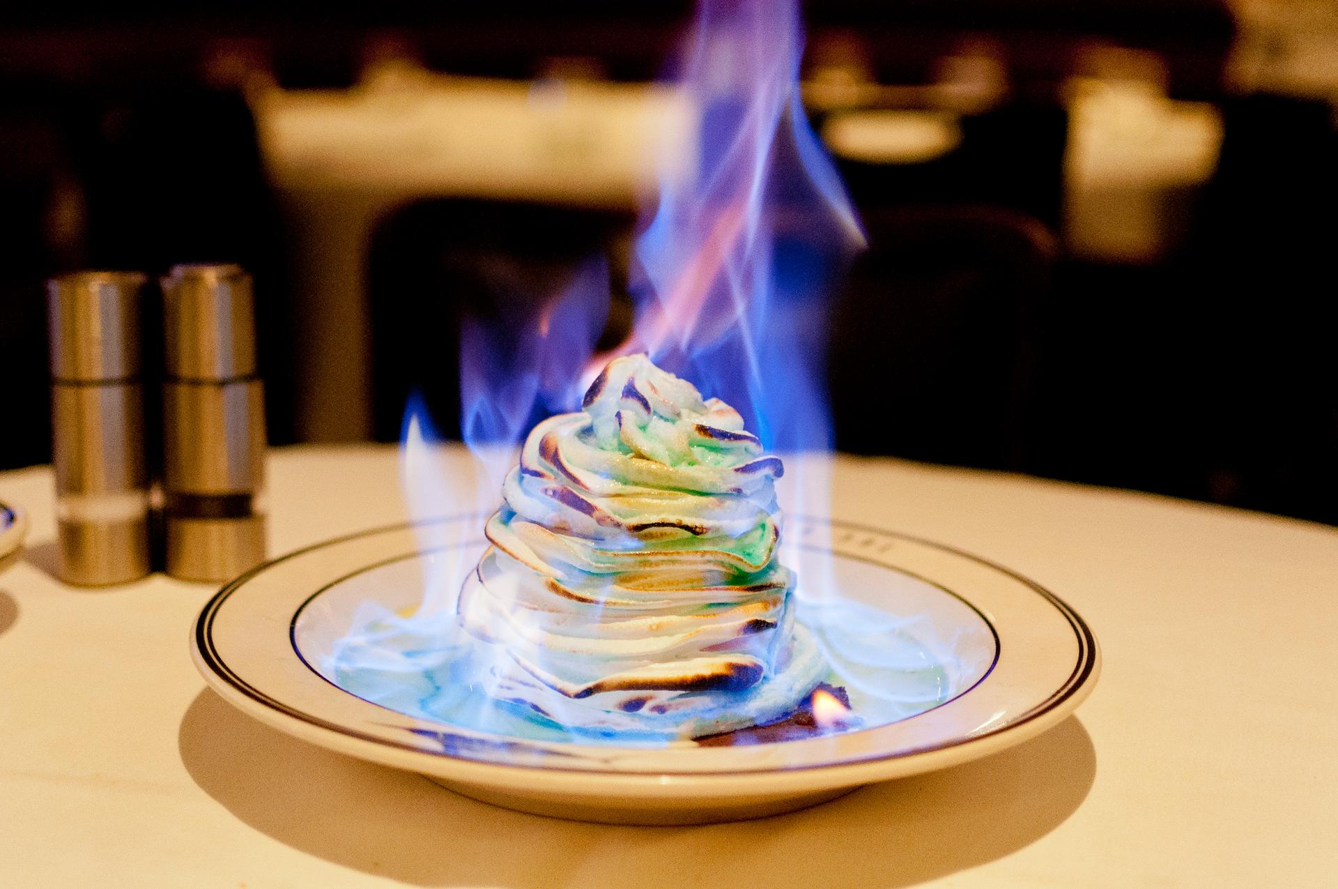 Zdjęcie przedstawia porcję lodów płonących leżących na porcelanowym talerzyku.