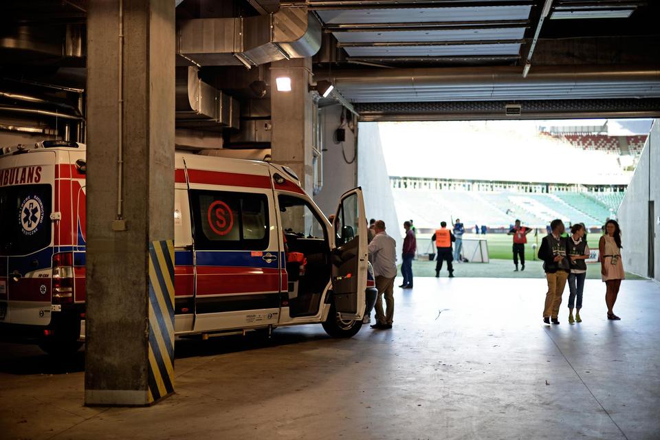 Galeria składa się zczterech zdjęć prezentujących służby uczestniczące wzabezpieczaniu imprez masowych. Zdjęcie numer cztery przedstawia bramę wjazdową na stadion. Betonowe słupy podtrzymują strop, po lewej za pierwszym znich karetka pogotowia ratunkowego. Karetka to furgonetka stojąca bokiem do obserwatora, przodem wkierunku wejścia na stadion znajdującego się wgłębi po prawej stronie kadru. Boczne, rozsuwane drzwi karetki przymknięte, widoczna na nich litera Swczerwonym okręgu. Boczne przednie otwarte. Na tylnej szybie czerwony napis: ambulans. Wgłębi kadru, służby porządkowe wpomarańczowych kamizelkach.