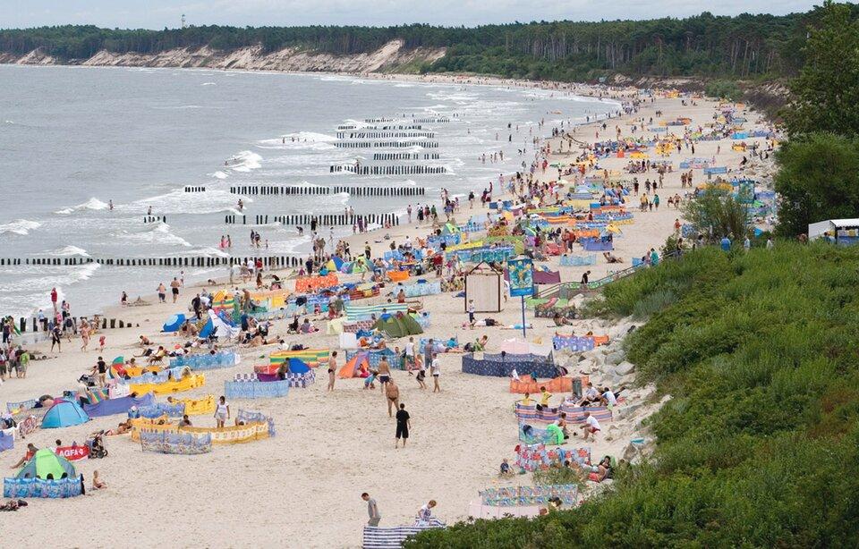 Na zdjęciu szeroka piaszczysta plaża, na plaży ludzie, parawany inamioty. Wmorzu falochrony – drewniane słupki ustawione rzędami prostopadłymi do brzegu. Wydmy niewysokie, porośnięte lasem.