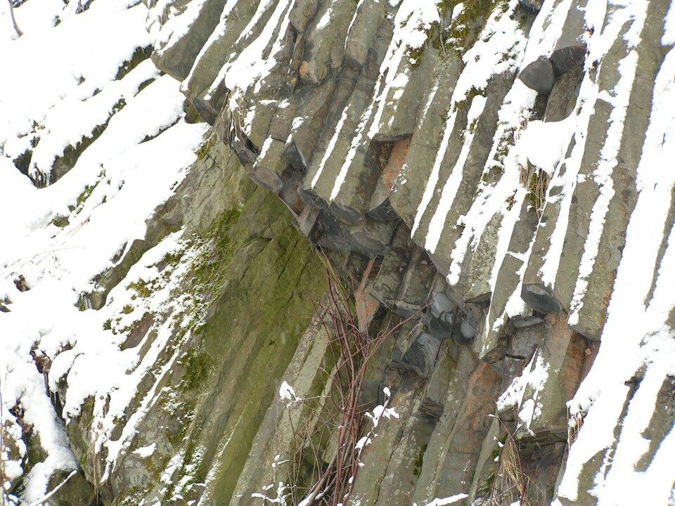 Na zdjęciu bazaltowe wielokątne wprzekroju słupy skalne na zboczu pokrytym częściowo śniegiem.