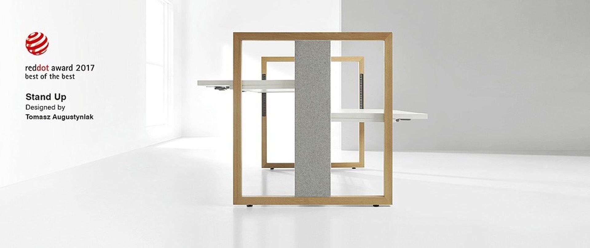 Ilustracja przedstawia biurko Tomasza Augustynia pt. Stand up. Boki to dwie kwadratowe ramy. Zgóry na dół boku idzie szara deska. Biurko po obu stronach ma białe blaty. Są na różnej wysokości.