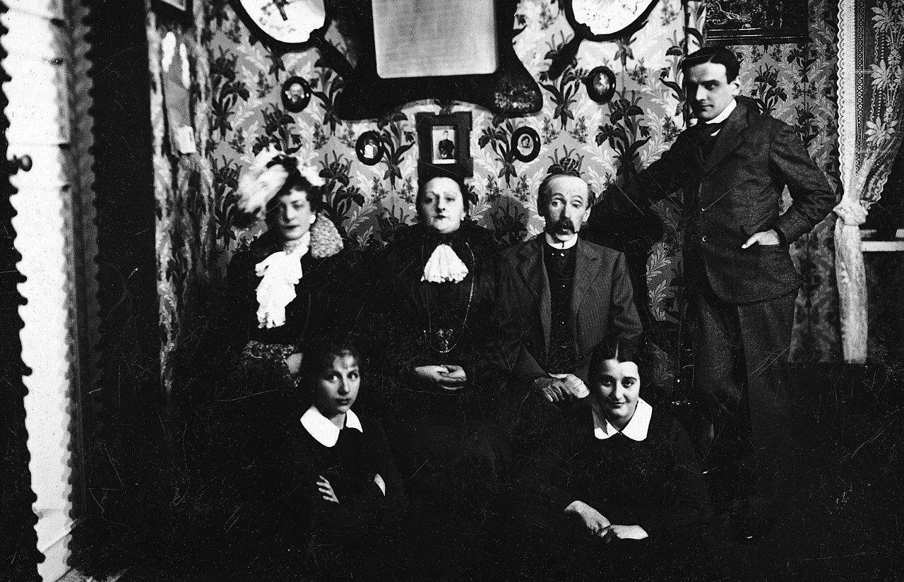 Zdjęcie przedstawia grupę aktorów grających wspektaklu Moralność Pani Dulskiej. To cztery kobiety idwóch mężczyzn. Obok siebie siedzą: dwie kobiety wśrednim wieku idojrzały mężczyzna. Pierwsza kobieta od lewej jest elegancko ubrana. na głowie ma nakrycie zpiórami. Siedząca wśrodku kobieta jest także ubrana elegancko. Trzyma na kolanach splecione ręce. Obok niej siedzi chudy, łysiejący, wąsaty mężczyzna. Jest ubrany wsurdut, kamizelkę, koszulę igarniturowe spodnie. Nieopodal niego stoi młody mężczyzna. Jest ubrany wgarnitur, koszulę ikrawat. Lewą rękę trzyma wkieszeni marynarki. Prawą opiera na stojącym nieopodal meblu. Ustóp siedzącej grupy widoczne są siedzące postacie dwóch młodych dziewczyn. Są ubrane wmundurki szkolne zbiałymi kołnierzykami. Jedna zdziewcząt się uśmiecha. Zdjęcie zrobione jest wpokoju mieszczańskiego domu. Na ścianie widać tapety bogato zdobione wroślinny motyw. Wisi tu także dużo obrazów.