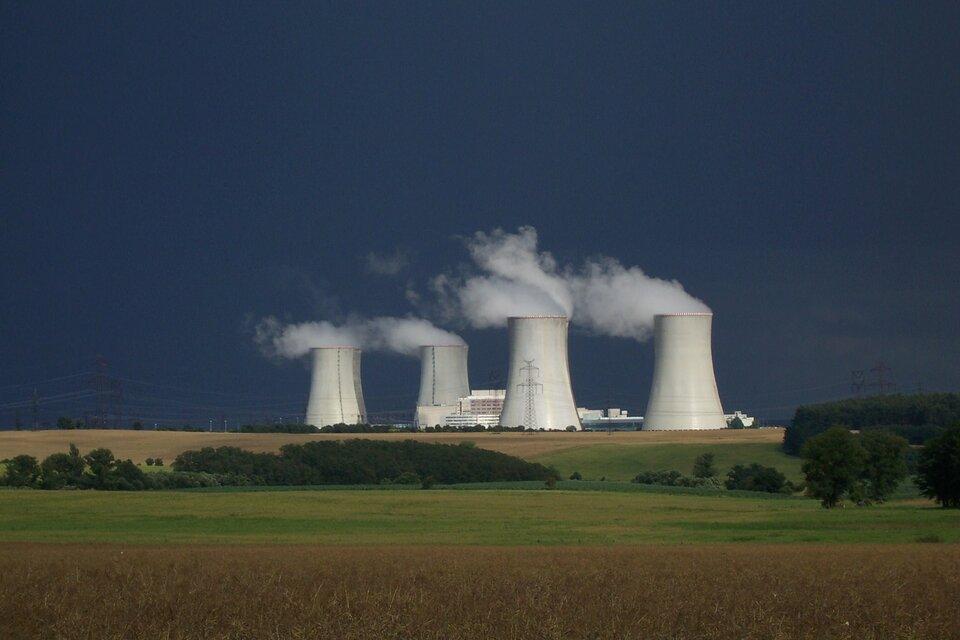 Zdjęcie przedstawia elektrownię atomową widoczną na horyzoncie zdjęcia krajobrazowego. Na pierwszym planie udołu kadru pola zbóż przetykane niewielkimi lasami. Niebo ciemnoniebieskie. Widoczne cztery kominy chłodnicze, zktórych wylatują kłęby skroplonej pary wodnej (mgły) iopołowę niższy, duży budynek pomiędzy nimi. Wokół kompleksu elektrowni znajdują się liczne linie energetyczne.