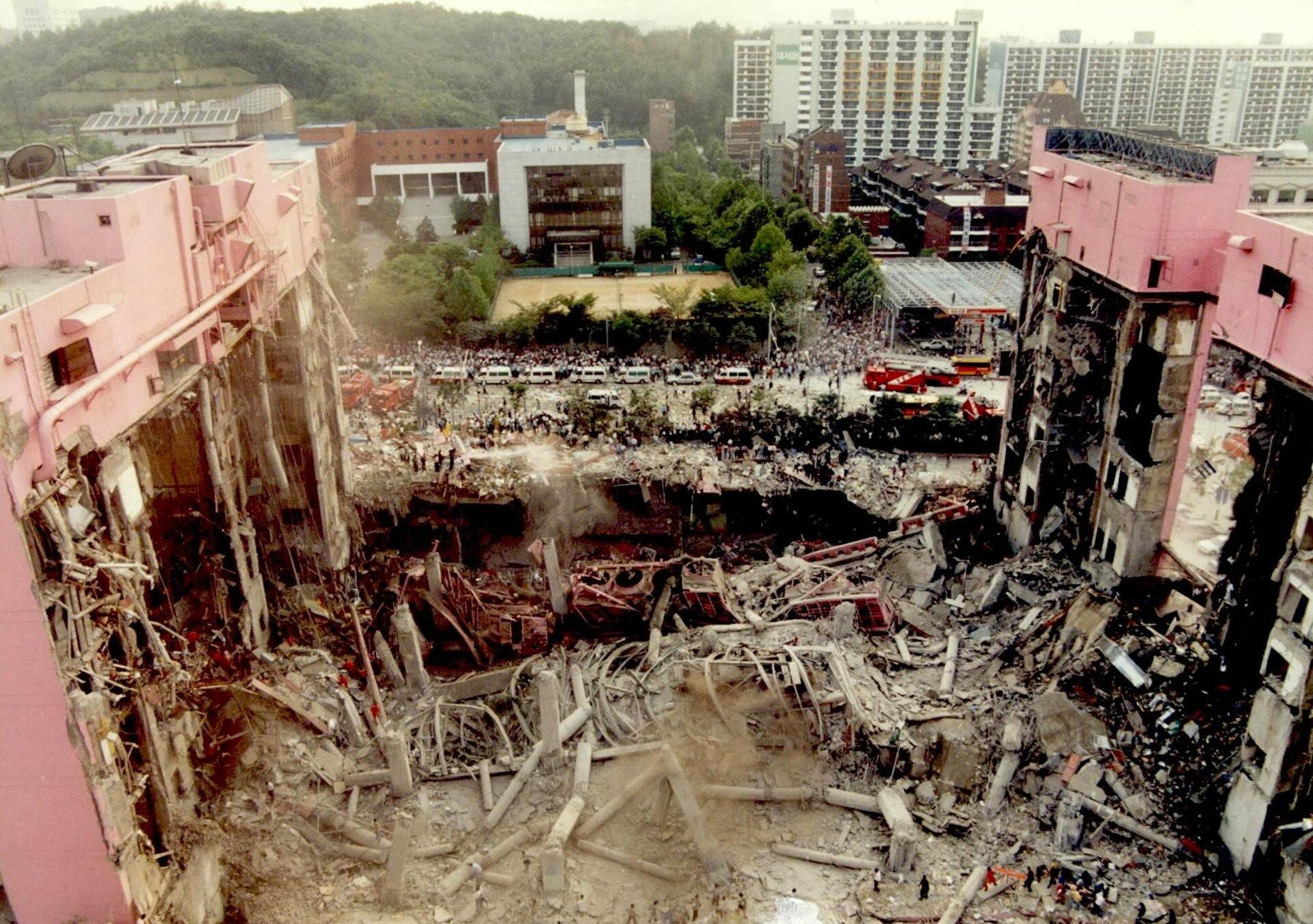 Zdjęcie przedstawia efekty katastrofy wgalerii handlowej wSeulu. Na pierwszym planie całkowicie zniszczona wewnętrzna część budynku galerii handlowej. Pięć pięter galerii zapadło się, pozostawiając jedynie widoczne na zdjęciu kawałki filarów zbetonu iowalnie zwinięte resztki stropów. Wokół ruiny pozostałych pięter wbocznych ścianach budynku. Na bocznych ścianach ocalałych skrzydeł zwisają części budynku. Udołu kadru oraz wtle sceny ludzie. Grupy osób przeszukują zgliszcza budynku, wtle, za zgliszczami, ulica imiasto. Na ulicy setki osób przyglądających się. Wzdłuż chodnika ustawione karetki pogotowia. Na prawo od karetek samochód straży pożarnej – jeden zwielu obecnych wkadrze, lecz najbardziej wyraźny ikompletny.