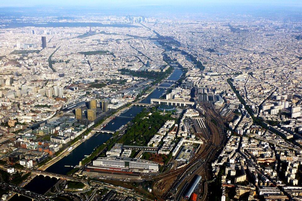 Na zdjęciu lotniczym gęsto zabudowane miasto, przez środek płynie rzeka.