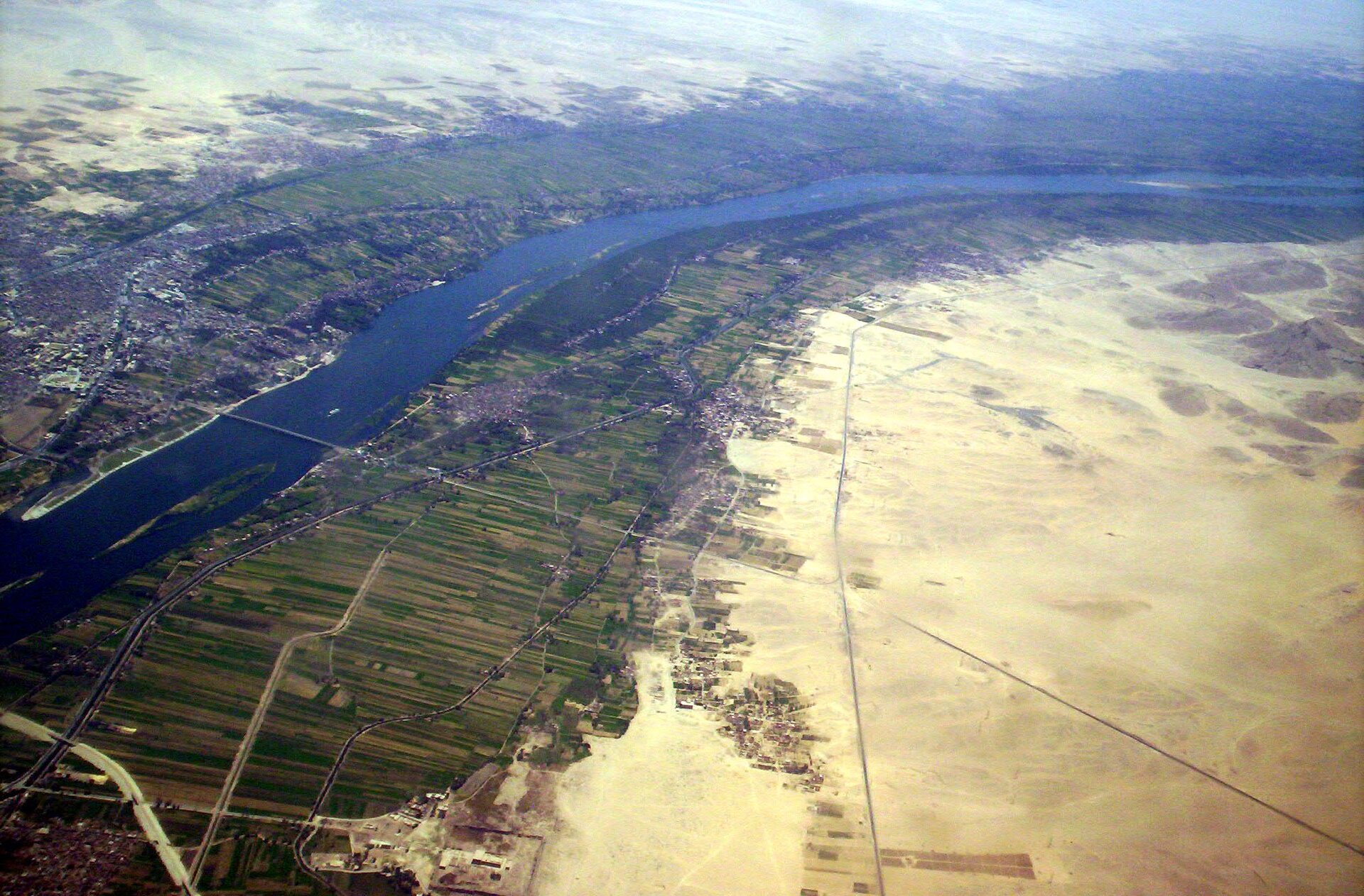Na zdjęciu lotniczym rzeka, brzegi zielone, pola uprawne, dalej od brzegów rzeki tereny piaszczyste całkowicie pozbawione roślinności.