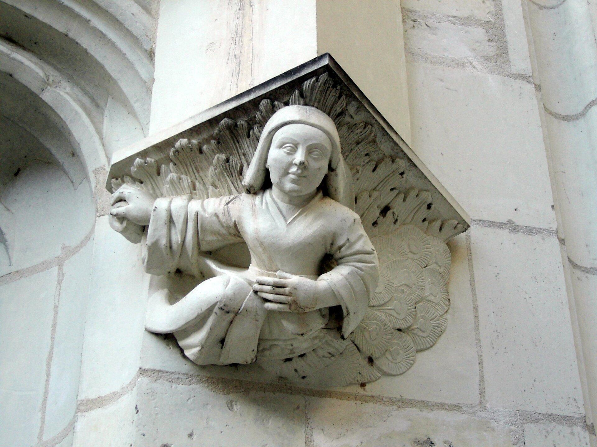 Ilustracja przedstawia ornament. Ukazuje on postać dziecka. Znajduje się ono na kamiennej ścianie. Lewą ręką trzyma się wpasie, natomiast prawą ma wyciągniętą wbok.