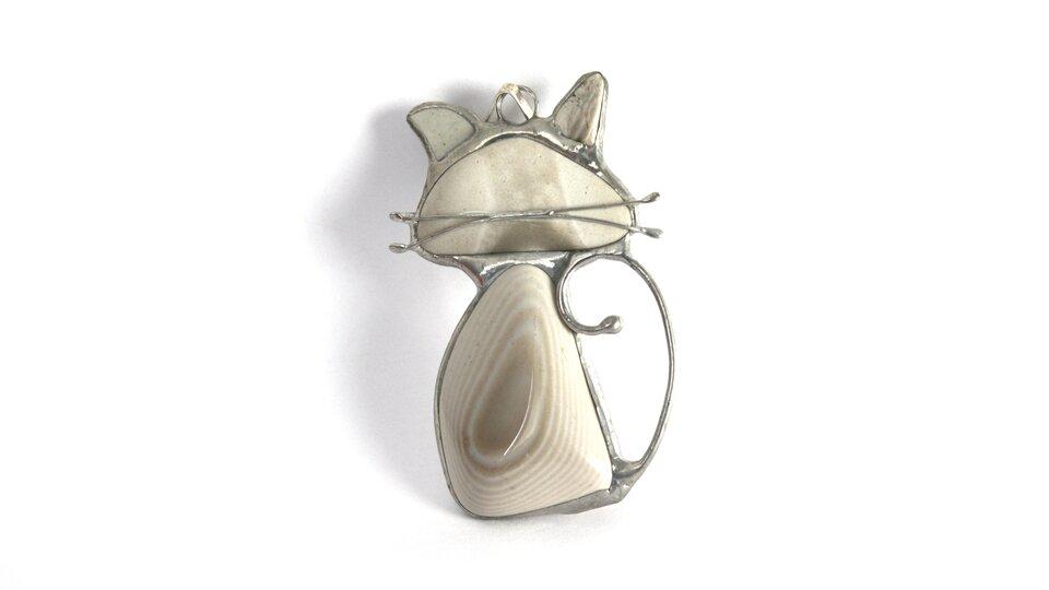Zdjęcie przedstawia przykład biżuterii zkrzemienia pasiastego, naszyjnik. Wmetalową, przypuszczalnie srebrną oprawkę wkształcie kotka wprawiono cztery kawałki krzemienia pasiastego. Największy, owyraźnym biało beżowym wzorze tworzy brzuch kota, nieco mniejszy beżowy to głowa, adwa najmniejsze wypełniają przestrzeń na uszy. Kotek ma również wąsy zrobione zdwóch drucików zlutowanych zresztą metalowej oprawki iprzyklejonych do kamienia.