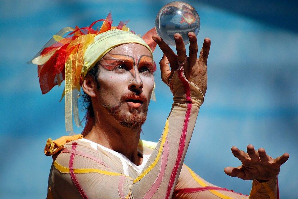 Zdjęcie przedstawia artystę ulicznego podczas występu prezentującego swoje umiejętności wżonglowaniu szklaną kulą. Artysta ubrany jest wbeżowy kostium wyszywany żółtymi, czerwonymi iróżowymi paskami, podobne paski ma we włosach oraz namalowane na twarzy. Szklaną kulę ośrednicy około dziesięciu centymetrów trzyma wtrzech wyciągniętych palcach prawej ręki spoglądając na nią ze skupieniem.