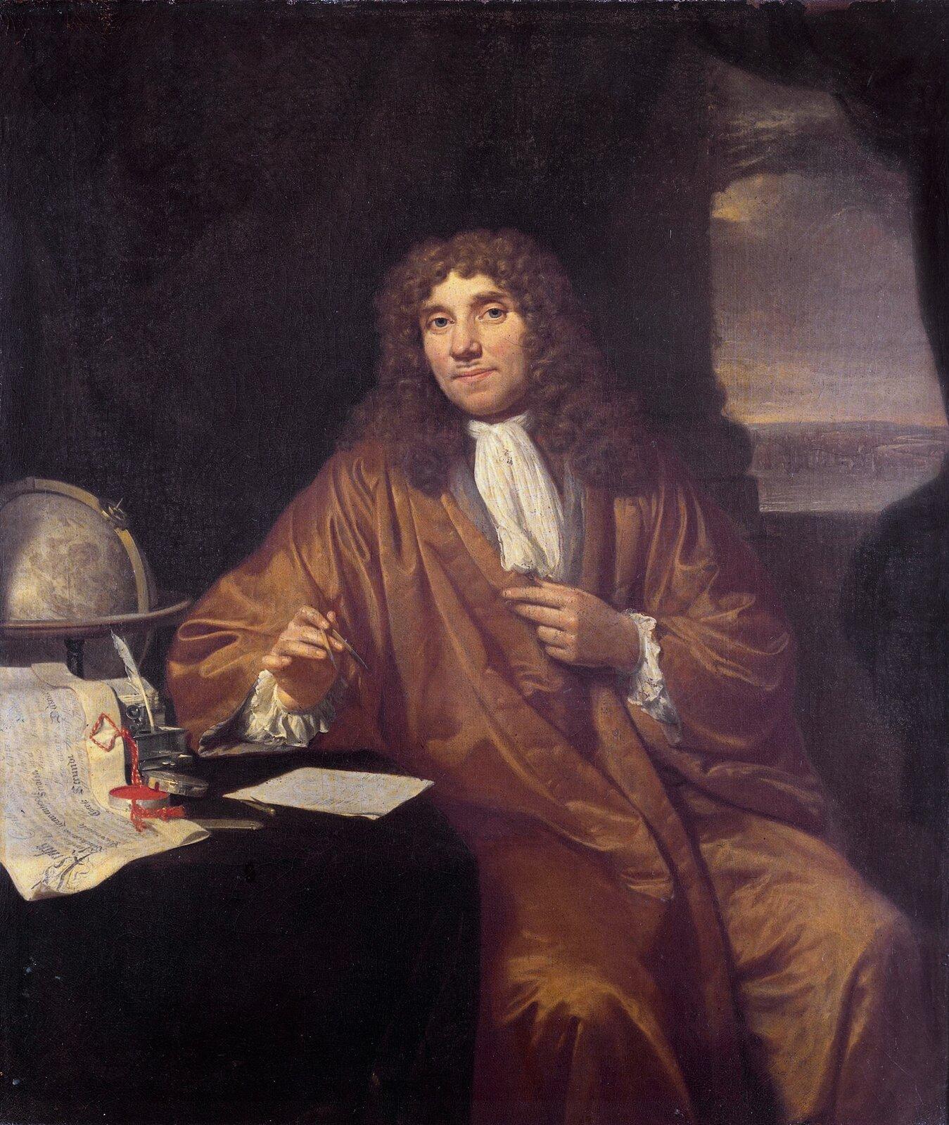 Portret mężczyzny wstroju historycznym, mężczyzna ubrany wrodzaj długiego brązowego płaszcza. Siedzi bokiem przy stole. Na głowie peruka zdługimi kręconymi lokami.