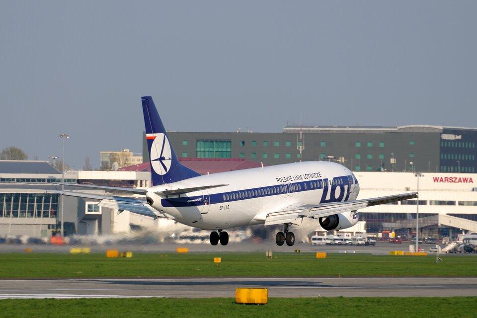 Duży pasażerski samolot startuje do lotu. Wtle budynki portu lotniczego.