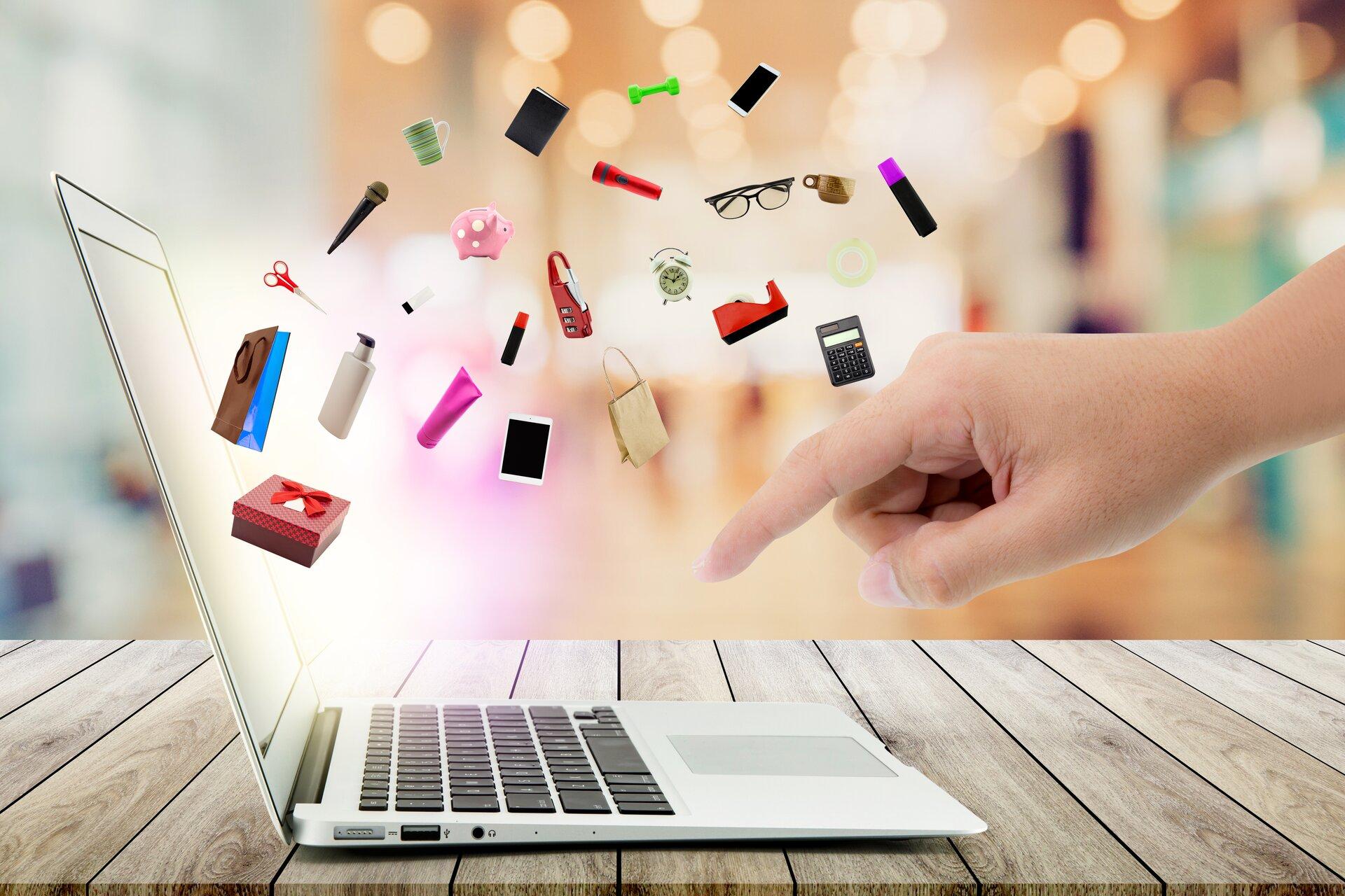 Ilustracja przedstawia zakupy przez Internet. Po prawej stronie wyłania się dłoń, która kieruje się wstronę klawiatury laptopa. Zekranu wypływają ikony takie jak: nożyczki, mikrofon, kubek, skarbonka, scyzoryk, telefon, torba, kalkulator, mazak, okulary, ciężarek, latarka.