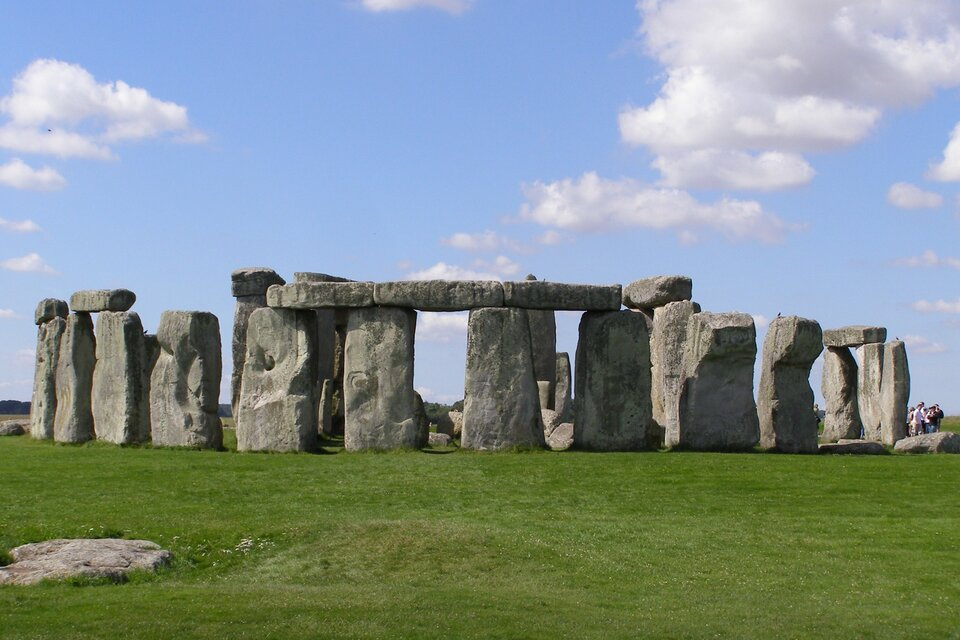 Zdjęcie przedstawia kamienny krąg Stonehenge widziany zodległości kilkudziesięciu metrów. Krąg zajmuje całą szerokość kadru, otaczają go tylko trawa iniebo. Na skraju kadru widoczna jest pomiędzy głazami niewielka grupa ludzi zapewniająca skalę porównawczą dla skał liczących do dziewięciu metrów wysokości.