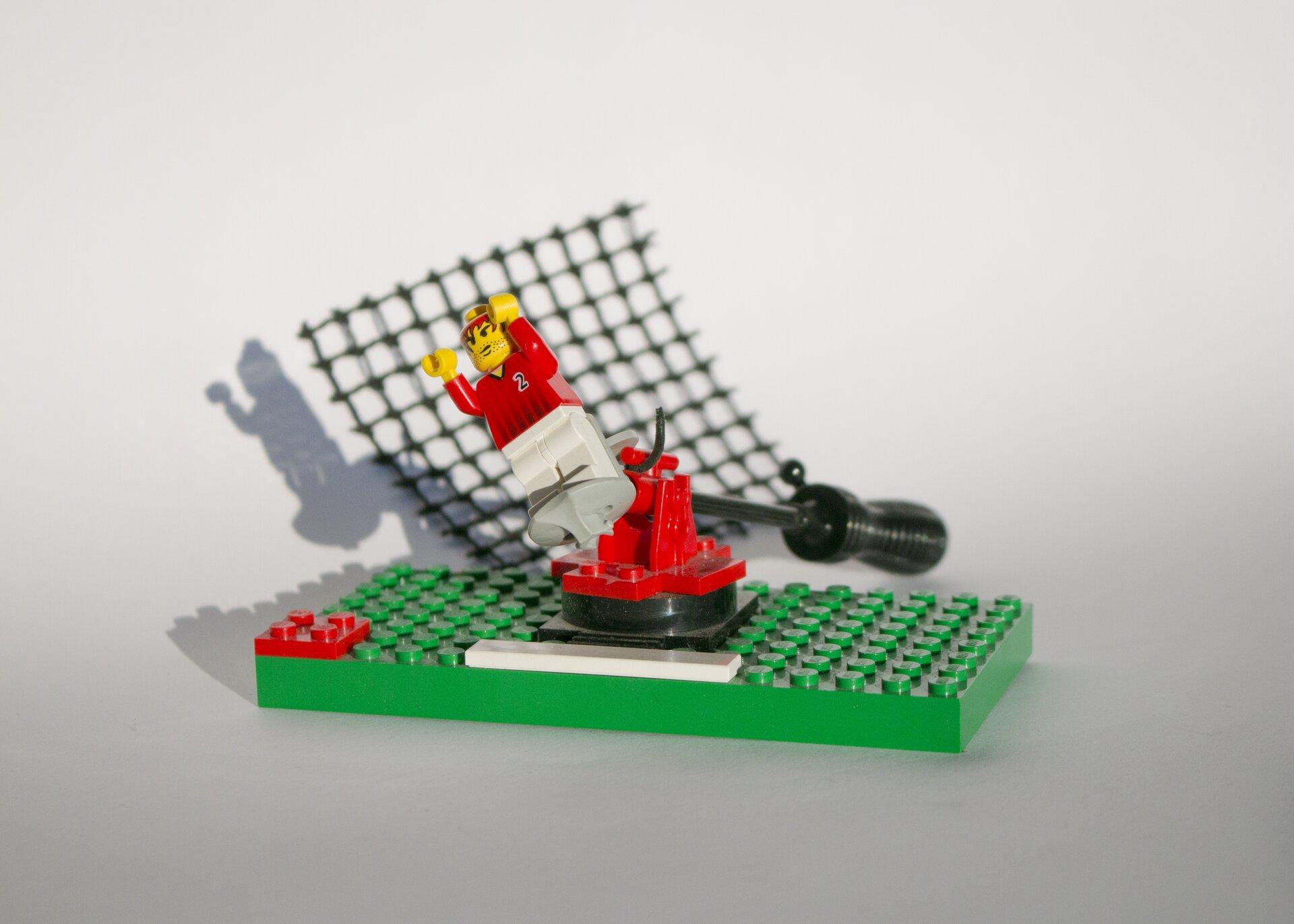 """Ilustracja przedstawia fotografię """"Lego"""". Wcentrum zdjęcia znajduje się duża, zielona platforma, do której przymocowane są klocki oraz biało-czerwono-żółty ludzik. Wtle znajduje się czarny śrubokręt iczarna, plastikowa siatka. Całość umieszczona jest na biało-szarym tle."""