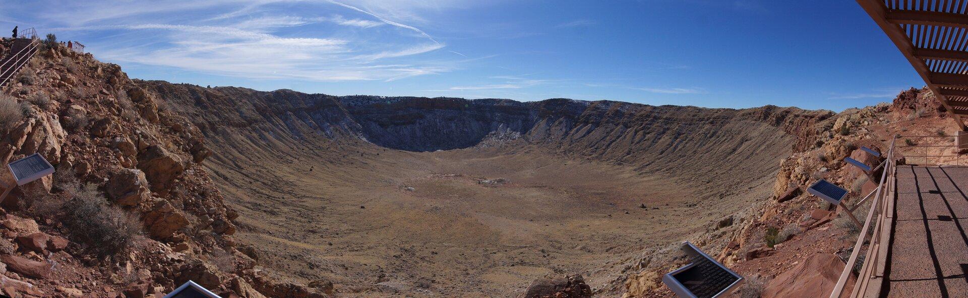 Fotografia prezentuje panoramę szerokiego igłębokiego wklęśnięcia wZiemi nazywanego kraterem.