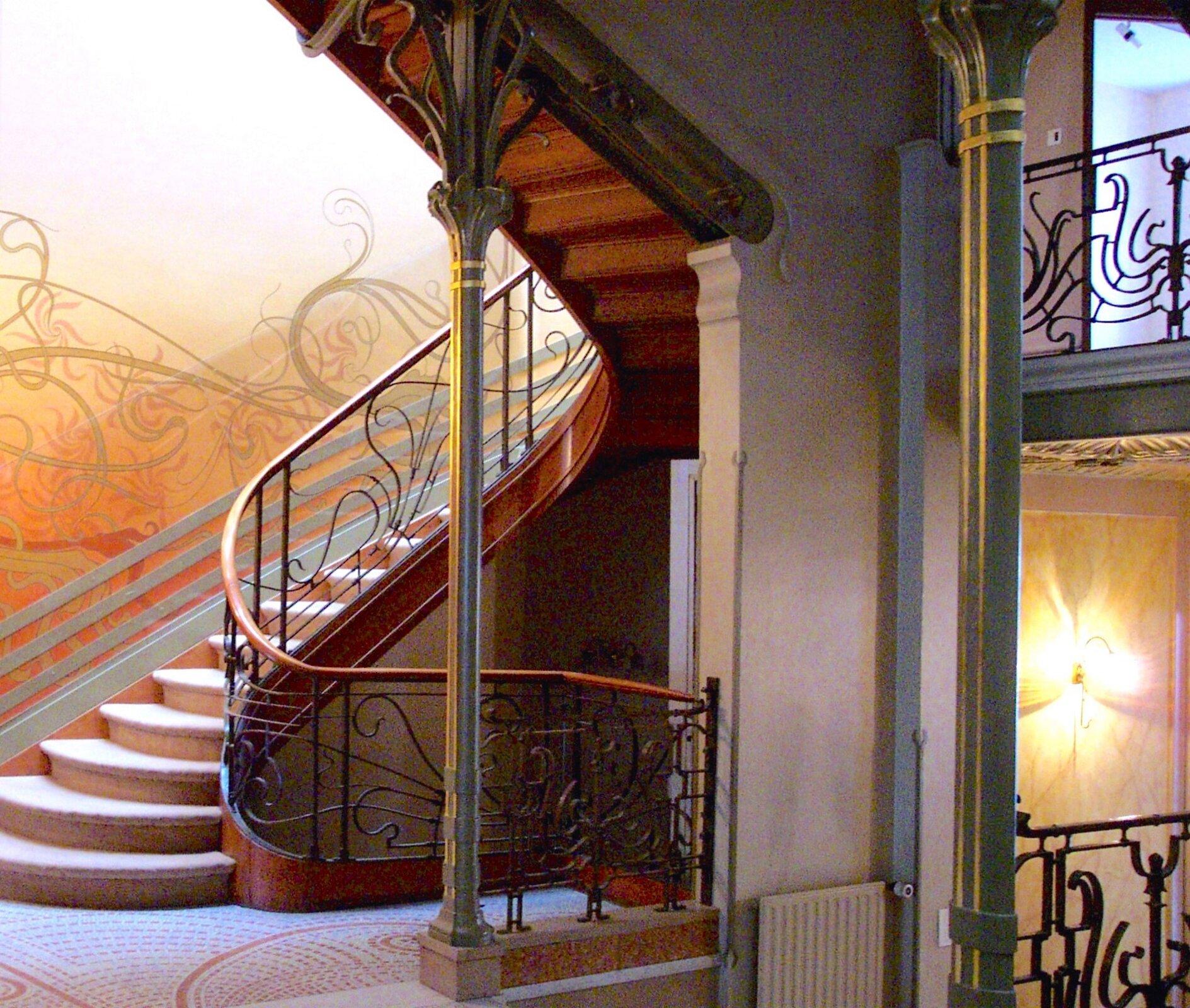 Ilustracja przedstawia klatkę schodową Hotelu Tassel wBrukseli. Jest to jeden znajbardziej rozpoznawalnych przykładów zdobnictwa secesyjnego, którego głównym elementem była charakterystyczna giętka, płynna linia. Na fotografii możemy dostrzec fragment schodów oraz korytarza.