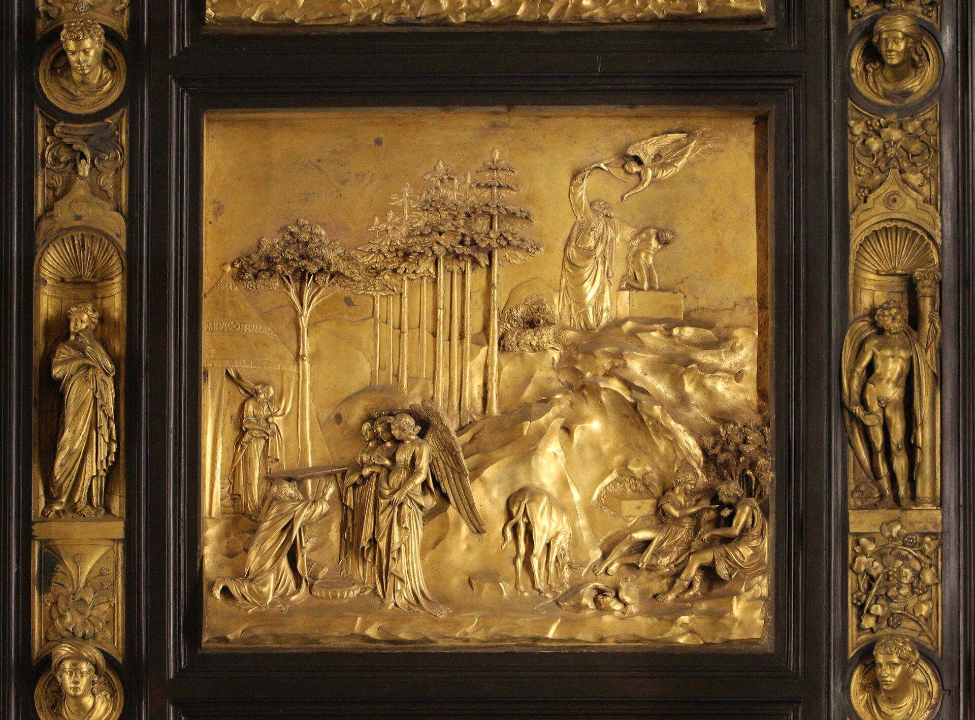 """Ilustracja przedstawia kwaterę """"Dzrwi Raju"""" Lorenza Ghibertiego. Ukazuje scenę zArbrahamem. Po lewej stronie klęczy Abraham, aprzed nim stoją dwaj aniołowie, Zbudowli przy krawędzi kwatery wychodzi trzeci anioł. Po prawej, upodnóża skały rozmawiają dwaj młodzieńcy. Na szczycie ukazana jest scena zOfiarą Izaaka. Abraham trzyma syna iunosi rękę zmieczem, by dokonać ofiary, jednak anioł nadlatuje ipowstrzymuje starca., chwytając jego miecz."""