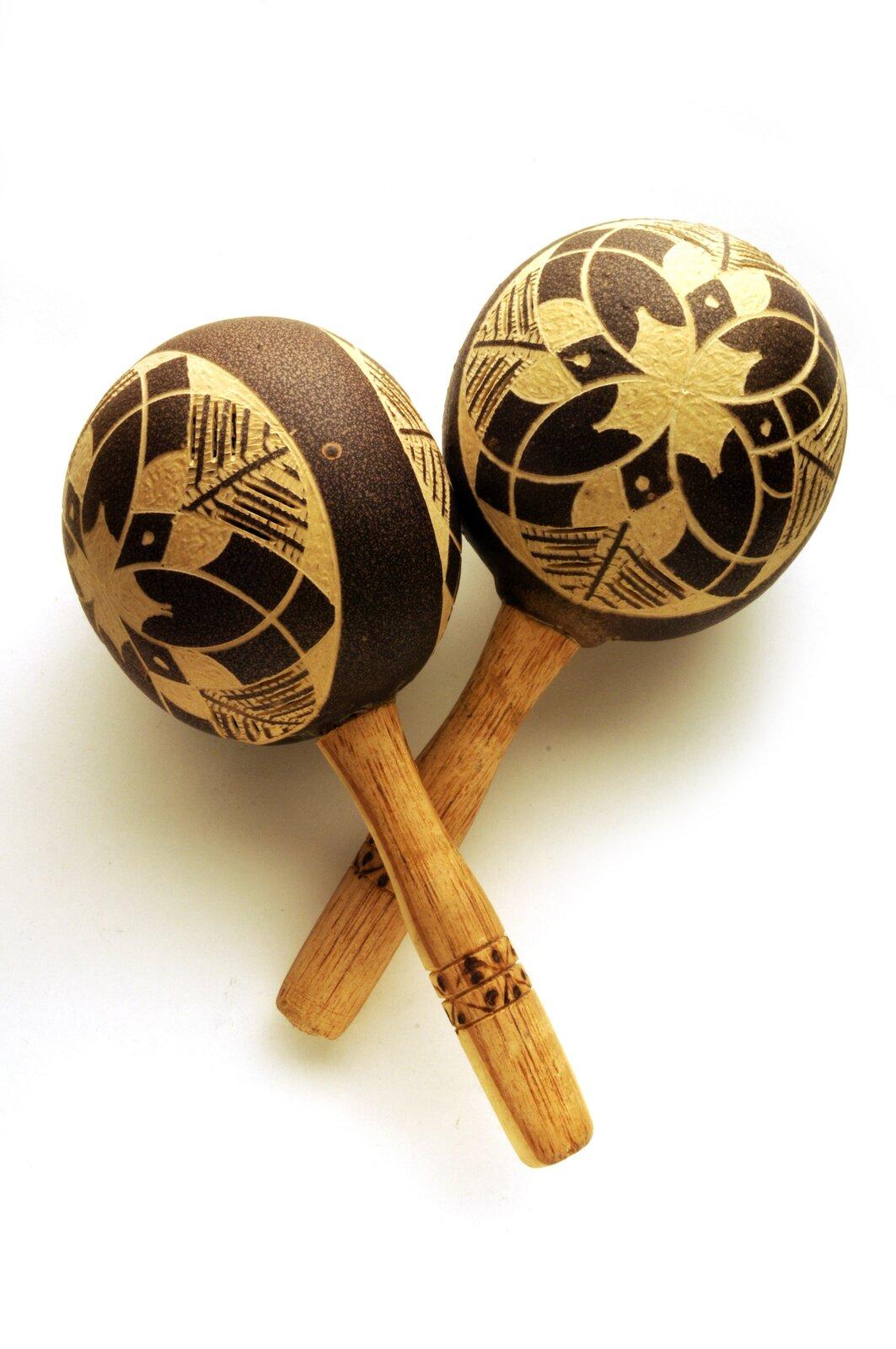 Ilustracja przedstawia instrument samobrzmiący – marakasy. Instrument ten składa się zkorpusu oraz trzonka. We wnętrzu znajdują się twarde kamyki bądź nasiona, które przy potrząsaniu instrumentem powodują wydobywanie się dźwięku.