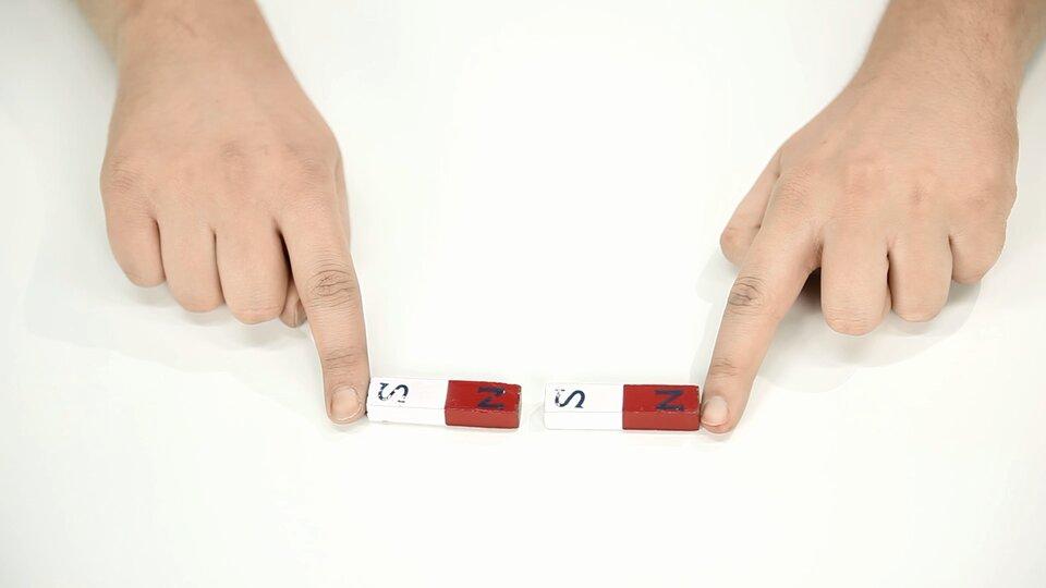 Fotografia przedstawia dłonie ucznia, który palcami wskazującymi przytrzymuje magnesy sztabkowe. Taki magnes posiada dwa bieguny: północny ipołudniowy. Przeciwne bieguny przyciągają się. Magnesy to prostokątne kafelki, które wpołowie są białe, awpołowie czerwone. Na magnesach umieszczono symbole biegunów. Wielka litera Sna białym tle to biegun południowy, awielka litera Nna czerwonym tle to biegun północny magnesu.