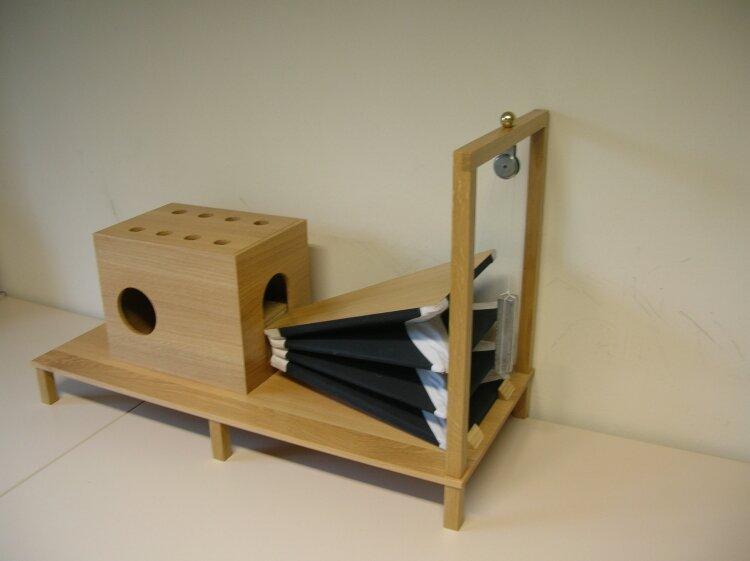 Drewniane urządzenie składające się zjednej strony ze skrzyni, wktórej górnej części znajduje się osiem otworów, awbocznej części jeden duży otwór, azdrugiej strony przymocowanego do tej skrzyni miecha ręcznęgo, dzięki któremu można wdmuchiwać powietrze do tej skrzyni. Na ramie przy miechu zamontowany jest mechanizm napędzający zciężarkiem.