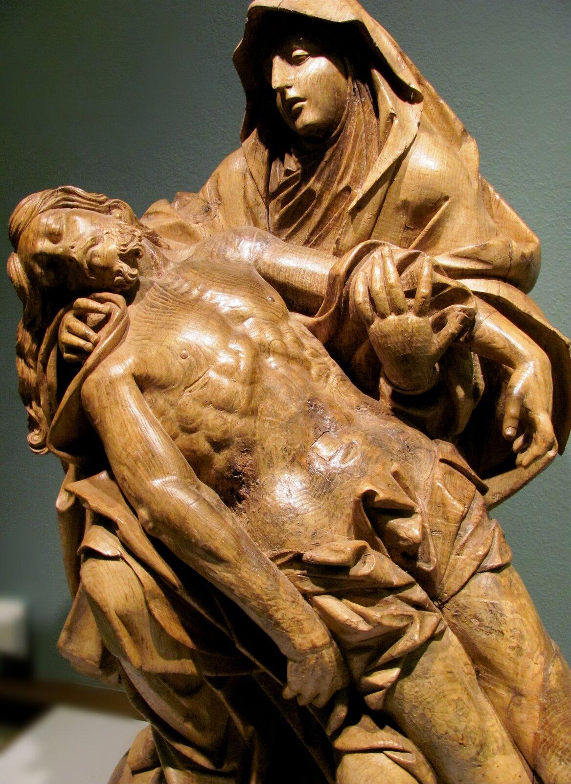"""Ilustracja przedstawia rzeźbę """"Pieta"""" nieznanego autorstwa. Wykonana zdrewna, przedstawia Maryję trzymającą wramionach ciało zdjętego zkrzyża Chrystusa. Wzrok Matki Boskiej skierowany jest na głowę Chrystusa, spoczywającą na prawym ramieniu Marii. Drugą ręką trzyma lewe ramię Syna. Ubrana jest wswobodny płaszcz, okrywający głowę. Ciało martwego Chrystusa bezwładnie osuwa się."""