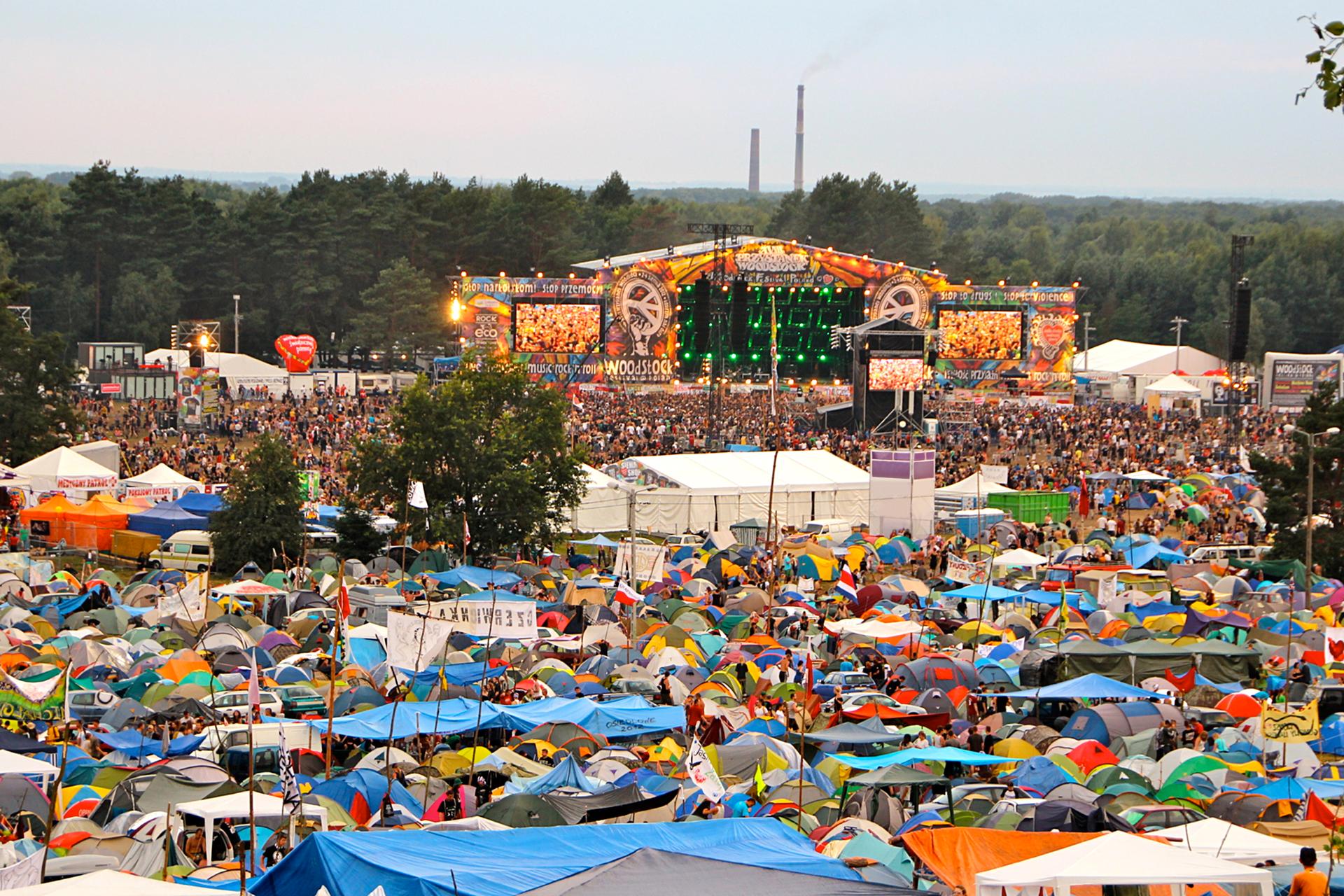 Galeria składa się zpięciu zdjęć prezentujących przykłady imprez masowych. Zdjęcie numer dwa przedstawia panoramę jednej zedycji festiwalu Przystanek Woodstock. Na pierwszym planie miasteczko namiotowe, kolorowe namioty gęsto rozłożone na całej powierzchni terenu. Wgłębi, za polem namiotowym, scena muzyczna. Wokół sceny kolorowe ścianki. Przed sceną tłum widzów. Za sceną gęsty las.