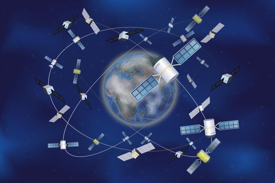 Ilustracja przedstawia planowane rozmieszczenie satelitów systemu Galileo. Tło niebiesko-granatowe, cieniowane. Wśrodku ilustracja Ziemi. Wokół Ziemi, białymi iszarymi liniami narysowano elipsy – orbity. Na elipsach, wróżnych miejscach, umieszczono satelity. Jest ich około 30.