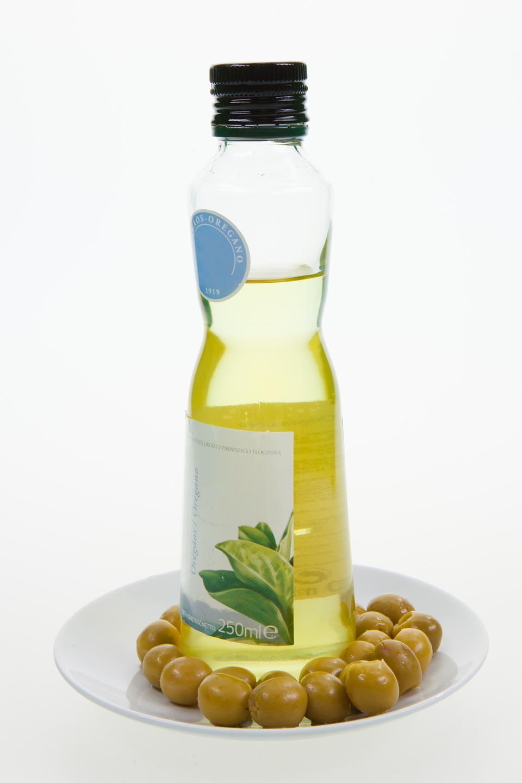 Fotografia przedstawiająca buteleczkę zoliwa zoliwek oraz rozłożone wokół niej liczne zielone oliwki