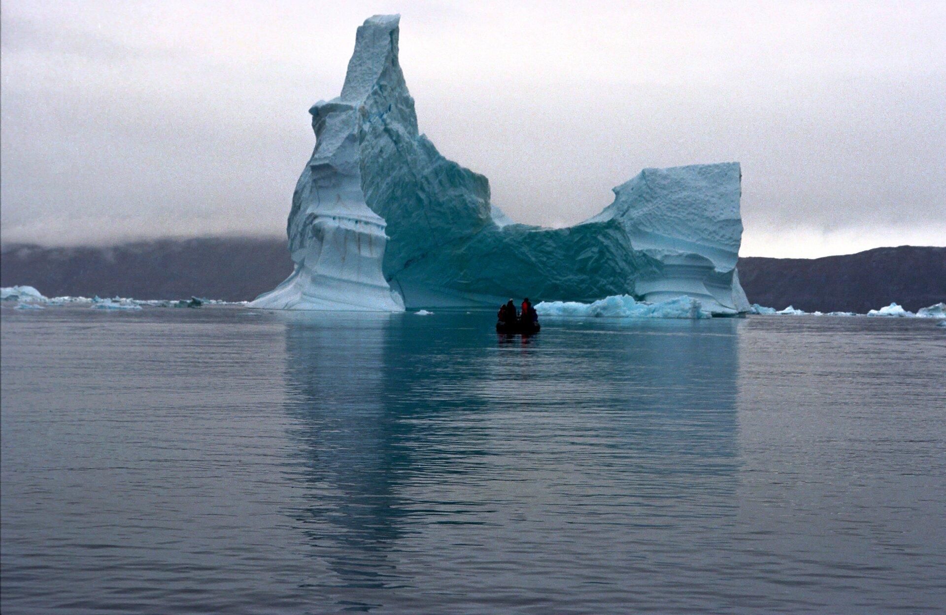 Na ilustracji góra lodowa wwodzie. Wtle pasmo górskie.