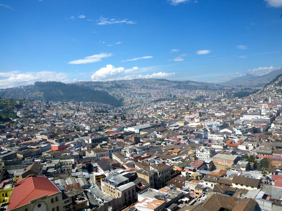Na zdjęciu lotniczym bardzo gęsta, niska zabudowa miejska. Wtle łagodne góry.