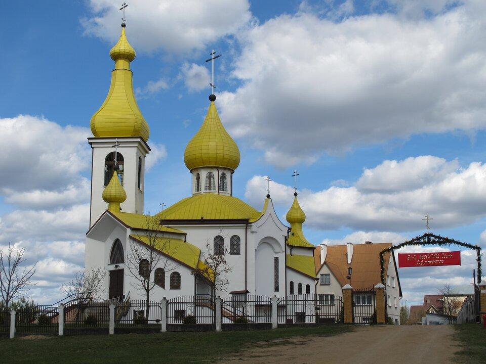 Na zdjęciu biała cerkiew zżółtym dachem ilicznymi wieżami zkopułami. Wtle zabudowania mieszkalne.