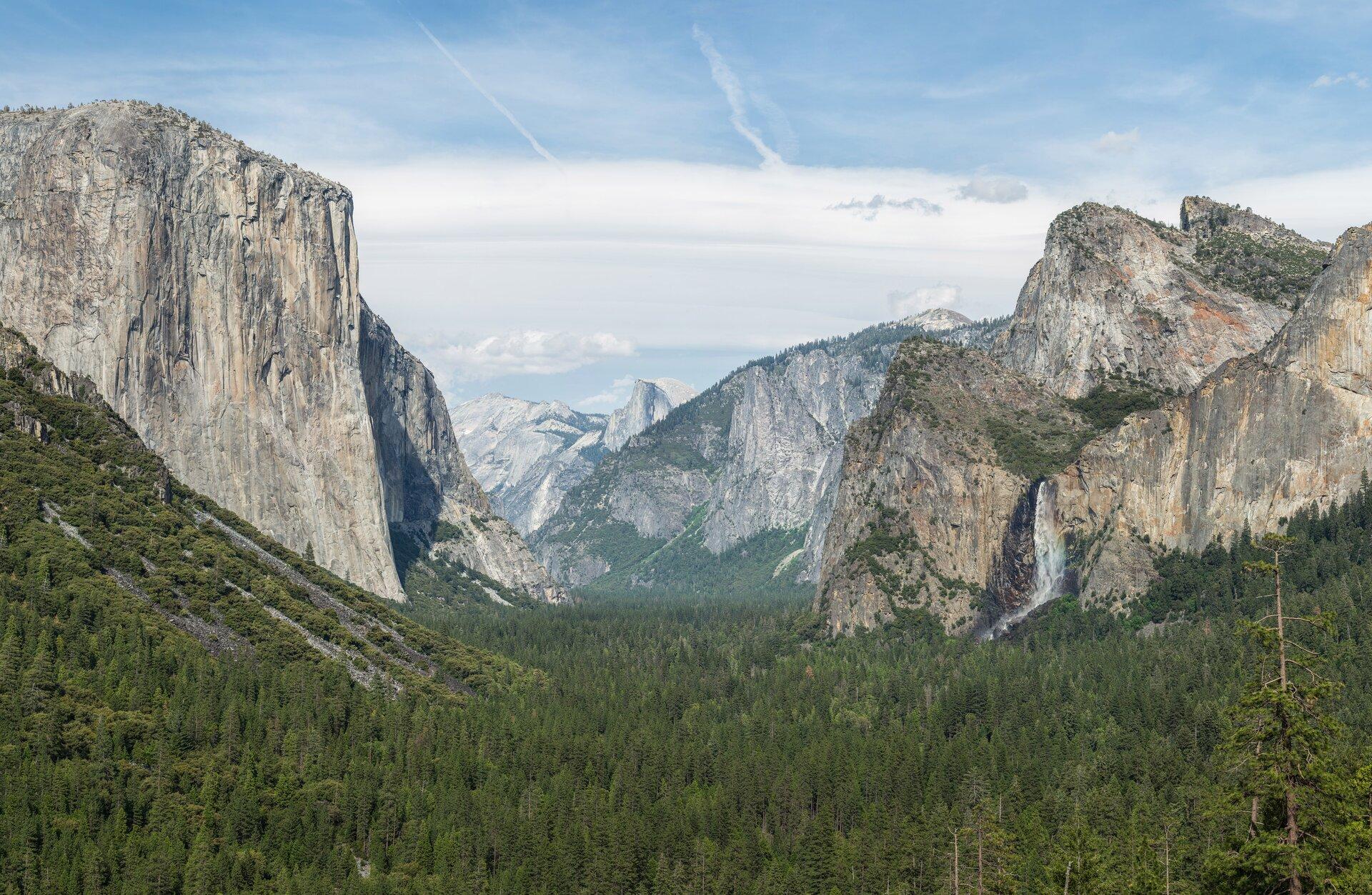 Zdjęcie przedstawia teren górzysty. Na pierwszym planie las iglasty. Po prawej ilewej stronie wysokie skaliste góry obardzo stromych, pionowych stokach. Wśrodku uskok porośnięty lasem iglastym. Woddali wysokie skaliste góry. Niebieskie niebo, białe chmury.