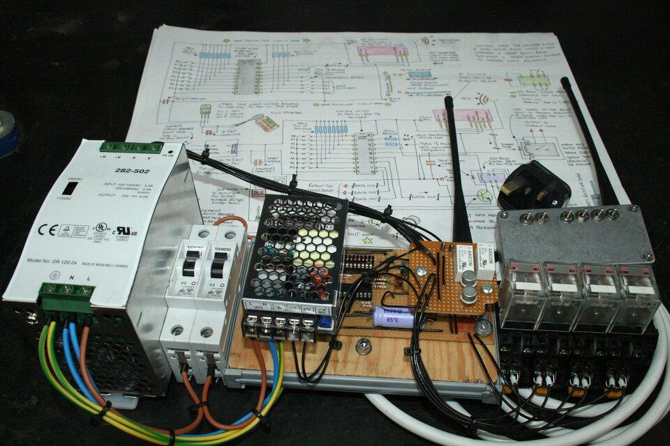 Zdjęcie przedstawia urządzenie elektroniczne domowej roboty składające się zkilku modułów połączonych ze sobą różnokolorowymi przewodami zamontowanych na metalowo drewnianej ramie. Uwagę zwraca obecność dwóch anten świadczących otym, że jest to jakiś rodzaj nadajnika. Urządzenie leży na pliku kartek, zktórych pierwsza, najlepiej widoczna jest narysowanym odręcznie schematem. Tło zdjęcia czarne.