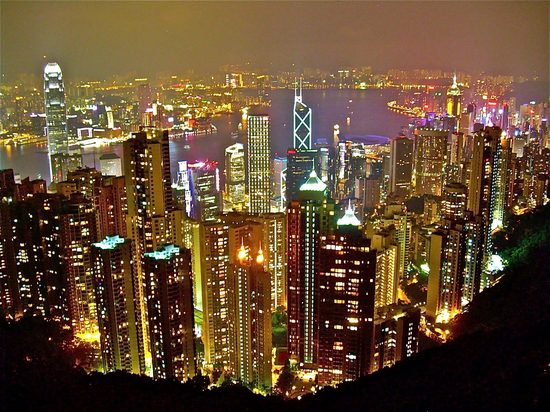 Zdjęcie przedstawia nocną panoramę Hong Kongu zwidocznymi na pierwszym planie rozświetlonymi licznymi drapaczami chmur. Prawie wszystkie budynki mają bardzo efektowną iluminację, wniektórych przypadkach ciągnącą się przez całe piętra. Światła miasta odbijają się od szklanych fasad sąsiednich budynków robiąc niezapomniane wrażenie.