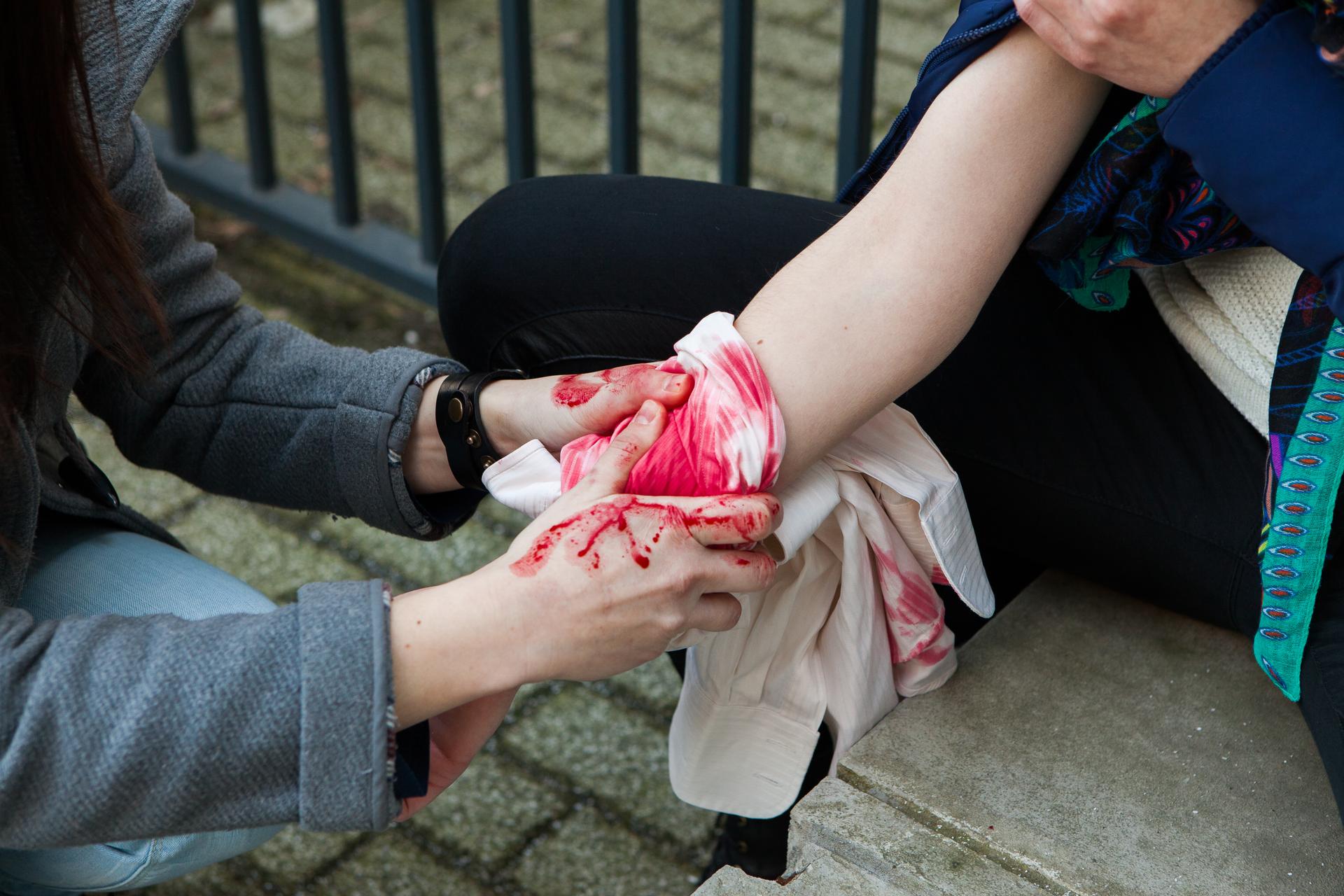Zdjęcie przedstawia opatrywanie rany na przedramieniu. Poszkodowany po prawej stronie zdjęcia. Ratownik po lewej stronie zdjęcia. Ratownik przytrzymuje biały materiał owinięty wokół przedramienia, powyżej nadgarstka. Dłonie ratownika bez rękawiczek ochronnych. Na dłoniach krew poszkodowanego.