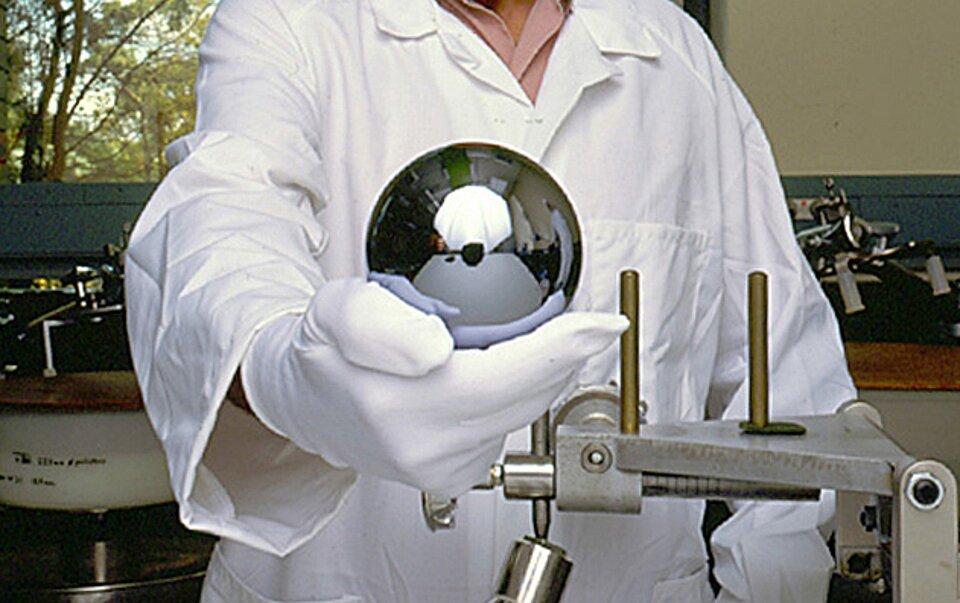 Zdjęcie przedstawia nowy wzorzec kilograma wykonany wramach projektu Avogadro zmonokryształu krzemu. Jest to jednocześnie najdoskonalsza wykonana przez człowieka kula na świecie, ajej średnica wynosi 93,75 mm. Idealnie gładka kula trzymana jest wdłoni wrękawiczce lateksowej przez naukowca, na tle pomieszczenia wypełnionego sprzętem badawczym.