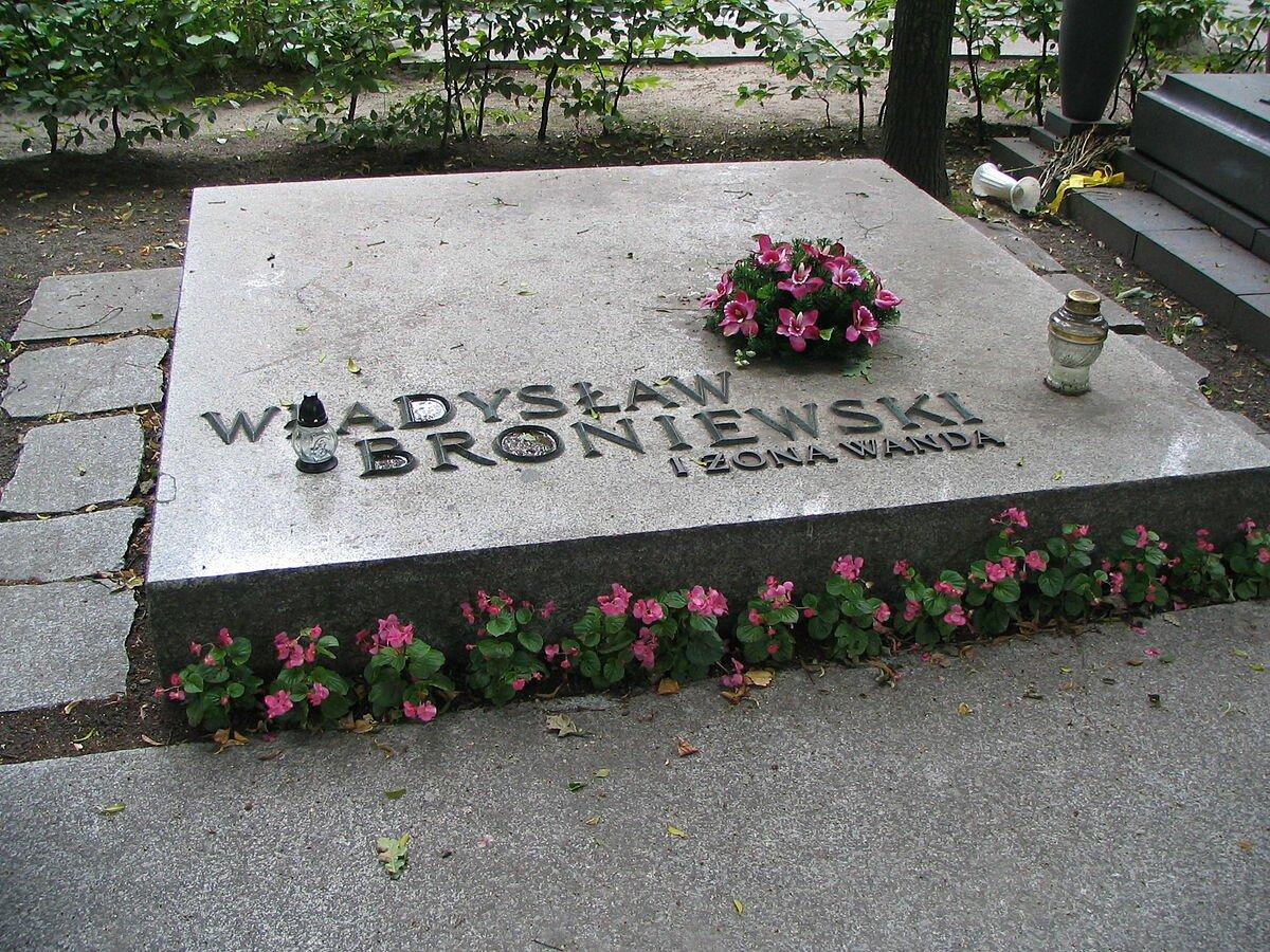 Płyta nagrobna znapisem Władysław Broniewski iżona Wanda. Na płycie stoją dwie lampki bez świeczek oraz leży mały wieniec zfioletowych kwiatów. Zziemi wzdłuż płyty wyrastają różowe kwiaty.