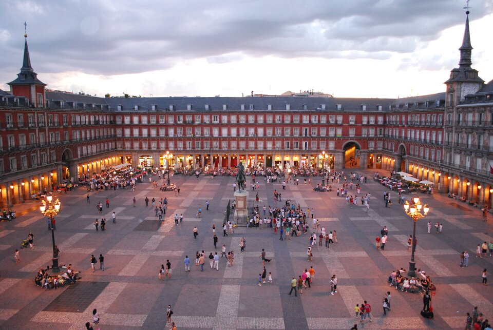 Na zdjęciu prostokątny plac otoczony trzypiętrowymi pomarańczowymi budynkami zdużą ilością balkonów. Wcentrum pomnik człowieka na koniu.