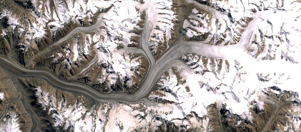 Na zdjęciu satelitarnym teren górzysty. Szczyty gór pokryte śniegiem. Wdolinie po prawej stronie biały pas zmrożonego śniegu przechodzący wszary po lewej stronie zdjęcia. Zmniejszych dolin wkierunku głównego lodowca spływają mniejsze jęzory.