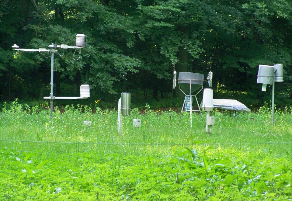 Zdjęcie przedstawia ogródek meteorologiczny. Ogródek otoczony jest płotkiem zsiatki. Wewnątrz ogródka znajdują się przyrządy meteorologiczne, wtym klatka meteorologiczna wkształcie drewnianego pudełka. Wewnątrz klatki znajdują się przyrządy pomiarowe. Na terenie ogródka widoczne są wiatromierz na wysokim słupie oraz deszczomierz.