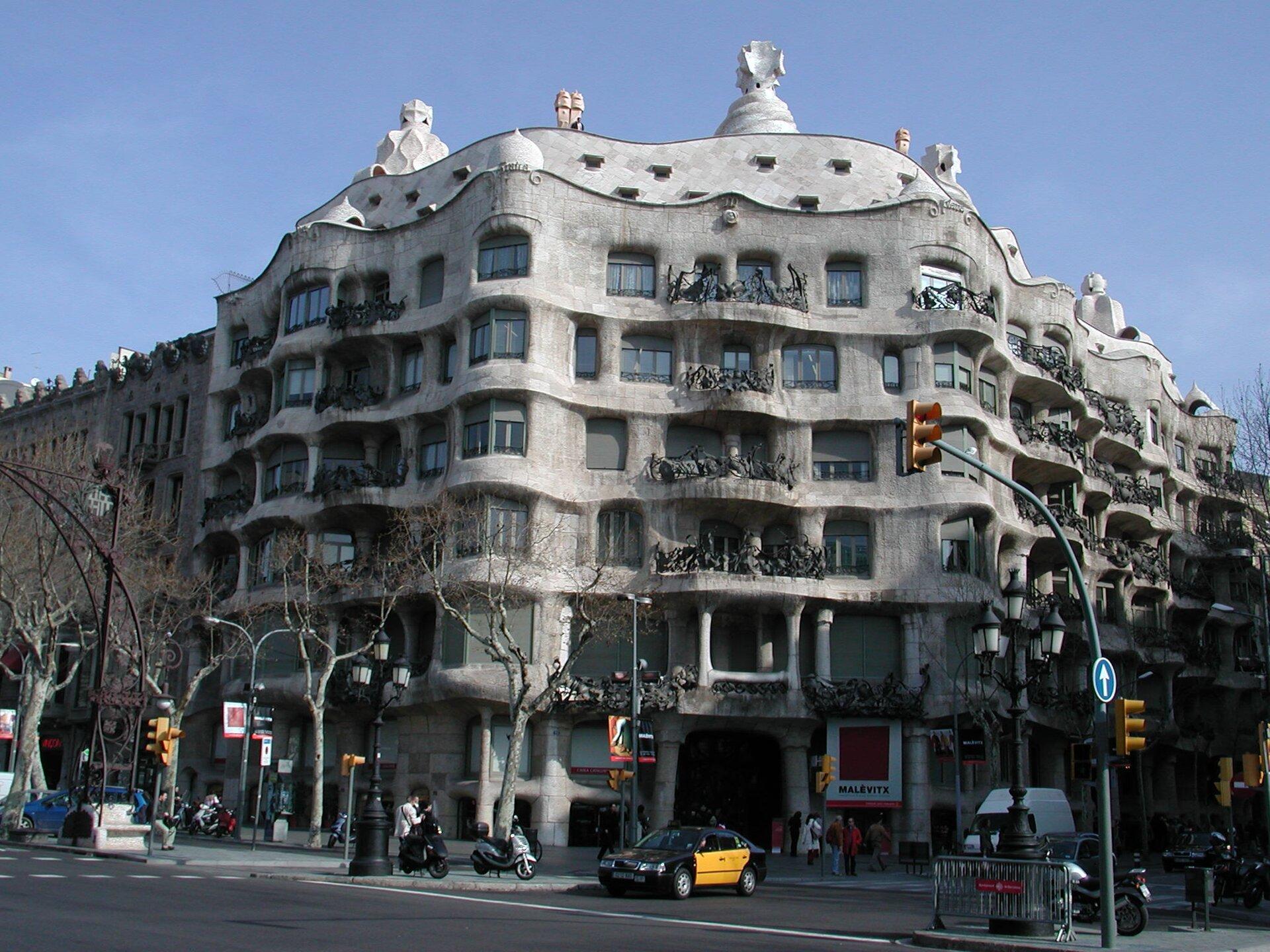 Ilustracja przedstawia budynek wBarcelonie autorstwa Antonio Gaudiego, Casa Mila. Budynek jest wielokondygnacyjny ima nieregularny kształt. Okna są duże, afasada budynku przypomina fale morskie. Wygląda ciężko imonumentalnie choć wzniesiona jest zcienkich wapiennych płyt. Balkony zdobią kute zżelaza balustrady przybierające kształt dzikich chaszczy. Ozdobą fasady głównej są również specjalnie rozmieszczone ptaki, które maja sprawiać wrażenie szykujących się do odlotu. Na zdjęciu jest również fragment ulicy, samochody, motocykle iludzie stojący przed wejściem. Wtle widać niebieskie niebo. Na ilustracji umieszczony jest niebieski pulsujący punkt. Po kliknięciu kursorem myszki wpunkt wyświetlą się dodatkowe informacje.
