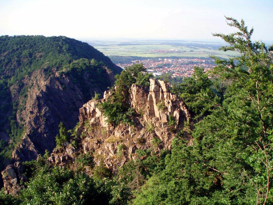 Na zdjęciu góry zrębowe, wysokie strome szczyty porośnięte roślinnością, ustóp gór na drugim planie, zabudowania.