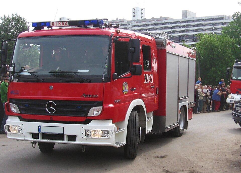 Galeria składa się zczterech zdjęć prezentujących służby uczestniczące wzabezpieczaniu imprez masowych. Zdjęcie numer dwa przedstawia wóz straży pożarnej ustawiony przodem do obserwatora. Czerwona szoferka, nad szybą zprzodu niebieskie światła. Czerwony napis straż. Za szoferką miejsca dla pozostałych strażaków zosobnymi drzwiami. Tył wozu strażackiego wkolorze srebrnym. Na dachu złożona drabina strażacka. Za wozem strażackim, grupa przyglądających się osób oraz daleko wtle za drzewami podłużny wysoki blok mieszkalny.