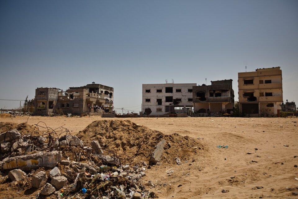 Na zdjęciu zniszczone budynki bez szyb woknach. Sterty gruzu.